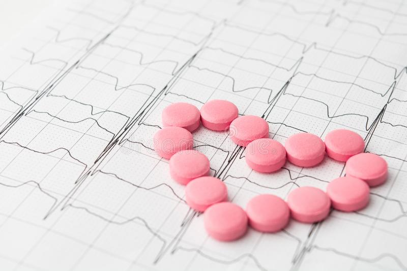 Heart of pink pills on paper cardiogram stock photography