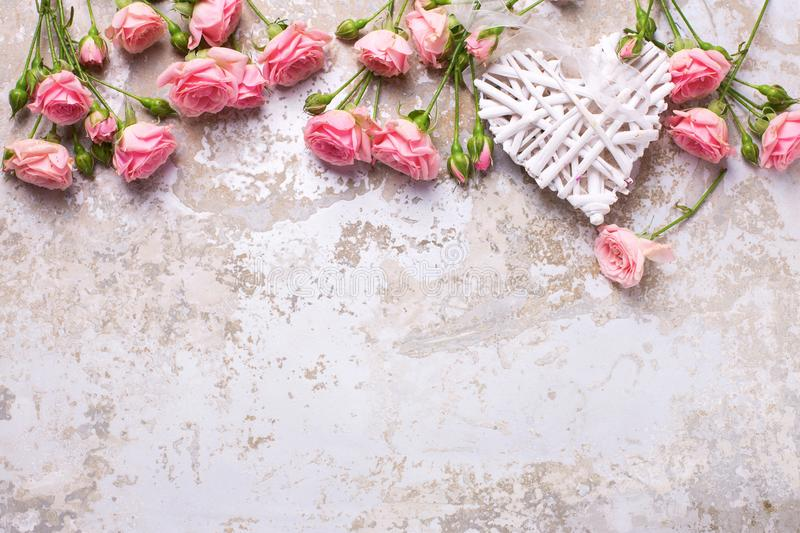 Heart and pink roses flowers on grey vintage textured background royalty free stock photo