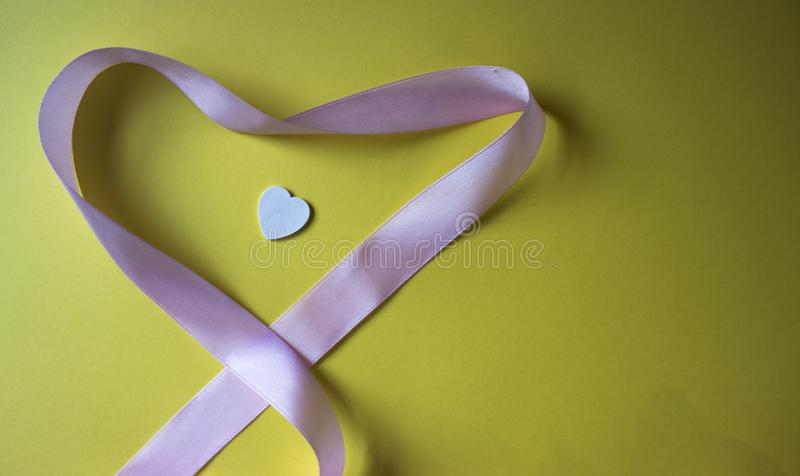 Heart pink shape ribbon and white heart on yellow background. Valentines day background. Top view with copy space royalty free stock photo