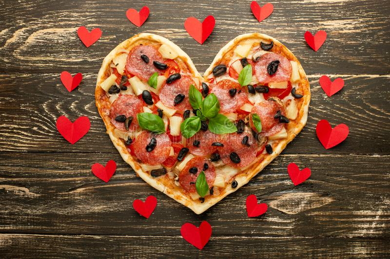 Heart pizza love concept Valentines day romantic dinner Italian pastry with red hearts. on a wooden table. Flat-lay stock photography