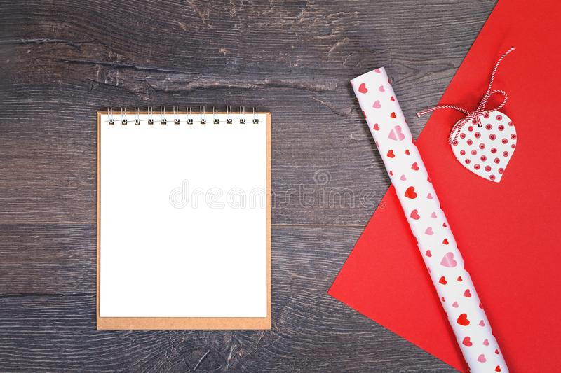 Heart and gift wrapping paper with notepad on wooden desk royalty free stock photography