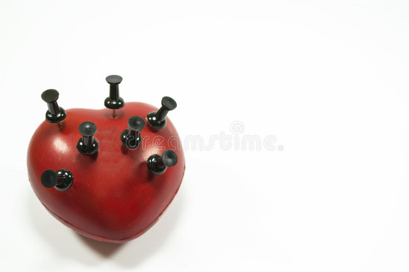 Heart and push pins. Red heart shape with black push pins puncturing it , conceptual image about heart related medical illnesses royalty free stock photography