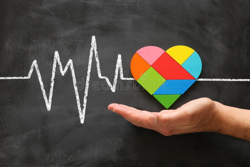 Heart puzzle over chalkboard, medical concept.  stock photo