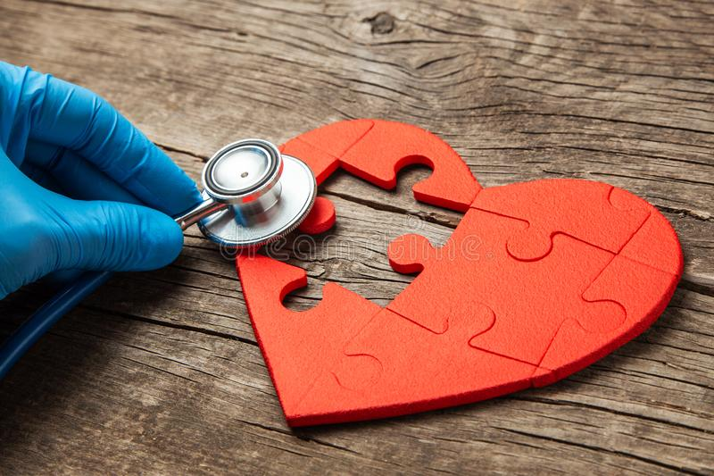 Heart puzzle red and stethoscope on wooden background. Concept diagnosis and treatment of heart disease, medical insurance royalty free stock photography