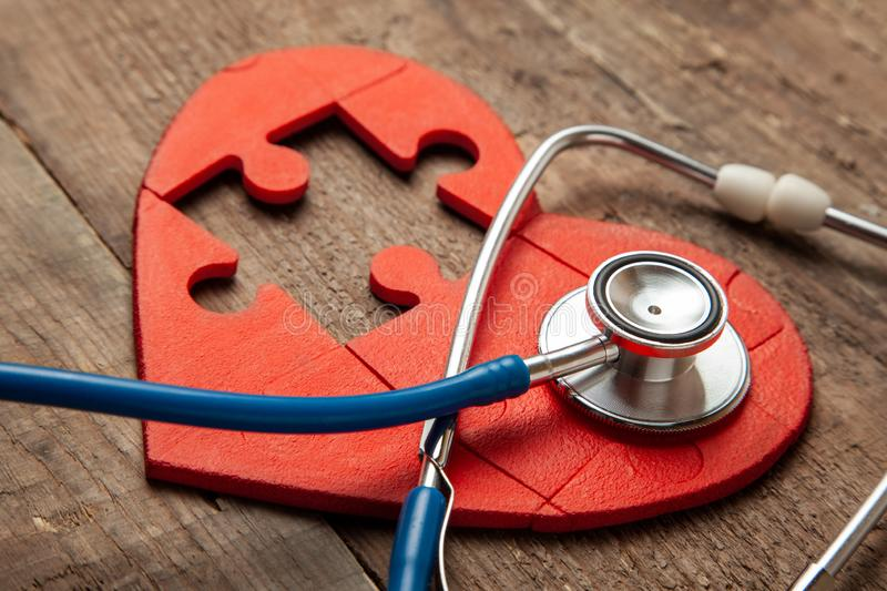 Heart puzzle red and stethoscope on wooden background. Concept diagnosis and treatment of heart disease, medical insurance stock photos