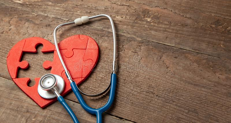 Heart puzzle red and stethoscope on wooden background. Concept diagnosis and treatment of heart disease, medical insurance royalty free stock photo