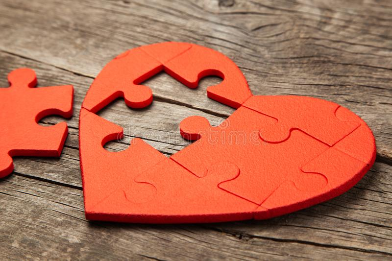 Heart puzzle red on a wooden background. Concept second half of the heart in love for Valentine`s Day or illness stock photography