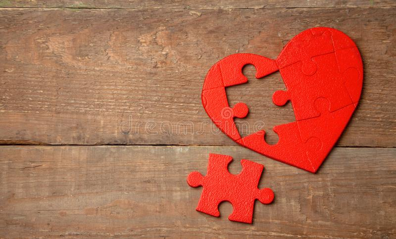 Heart puzzle red on a wooden background. Concept second half of the heart in love for Valentine`s Day or illness royalty free stock photo