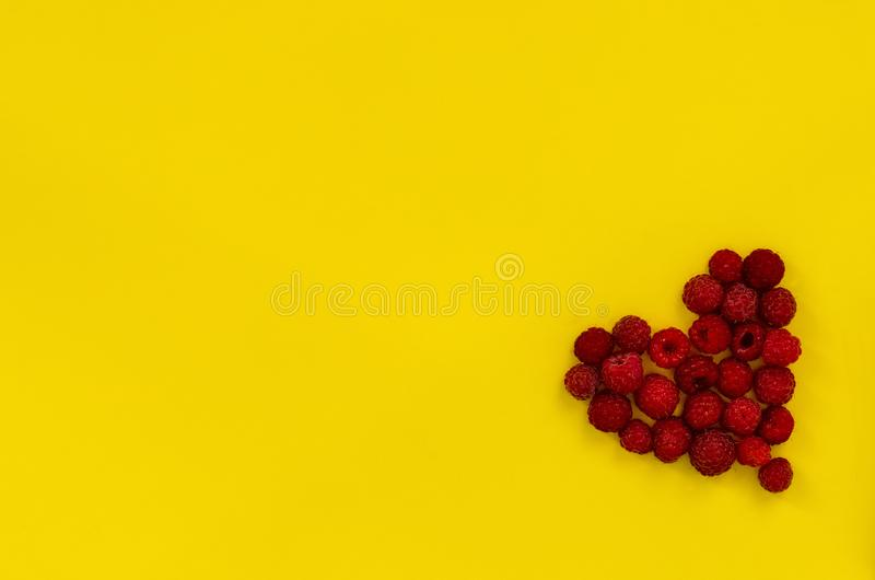 Heart of raspberries on yellow background. Colorful diet and healthy food concept. Background of raspberries. Top view. Copy space royalty free stock photo