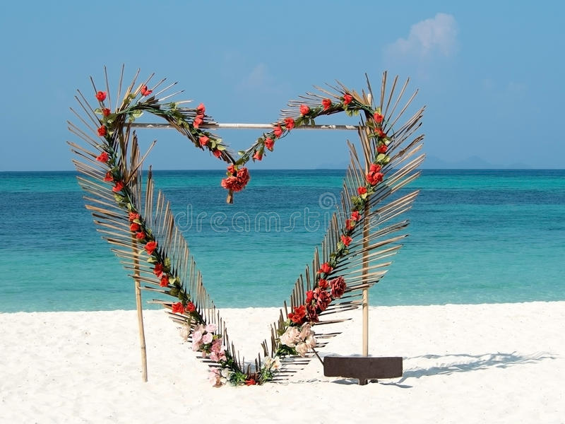 Heart from red flowers palm leafs on summer ocean beach background. Valentine, love, wedding concept. Clear sky, beautiful stock image