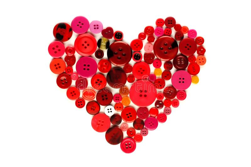 Heart of red and pink buttons. Heart shape made of red and pink buttons over a white background stock photography