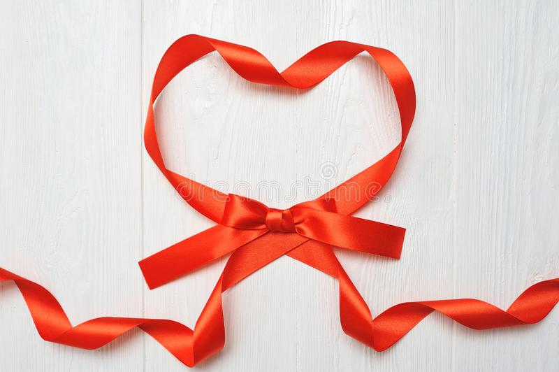 Heart from red ribbon on white wooden background. romantic love concept. valentines day background for birthday, holiday royalty free stock photo