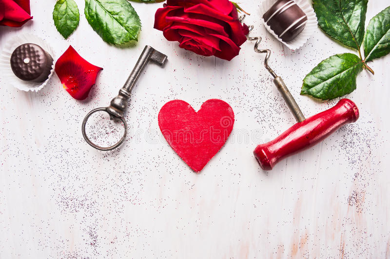 Heart, red rose, chocolate , key and corkscrew on white wooden, love background stock photography