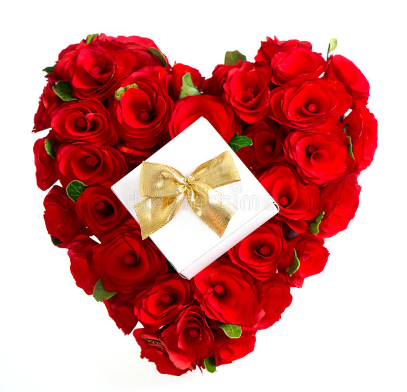 Heart of red roses with gift and golden bow. On white background stock images