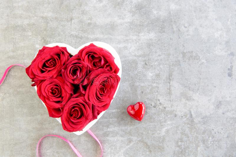 Heart of red roses on grey background with ribbon. Mother`s day, top view royalty free stock image