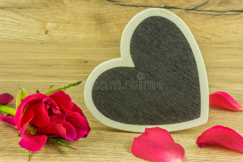 A heart with red roses. On a rustic wooden table stock photo
