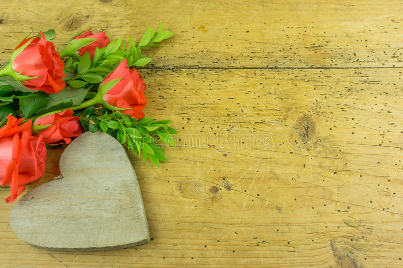 A heart with red roses. On a rustic wooden table stock photos