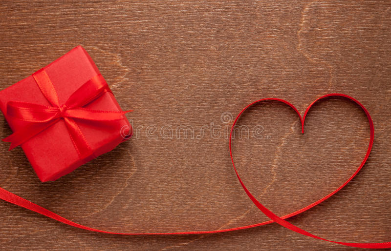 Heart of red tape and gift. Box on wooden background stock images