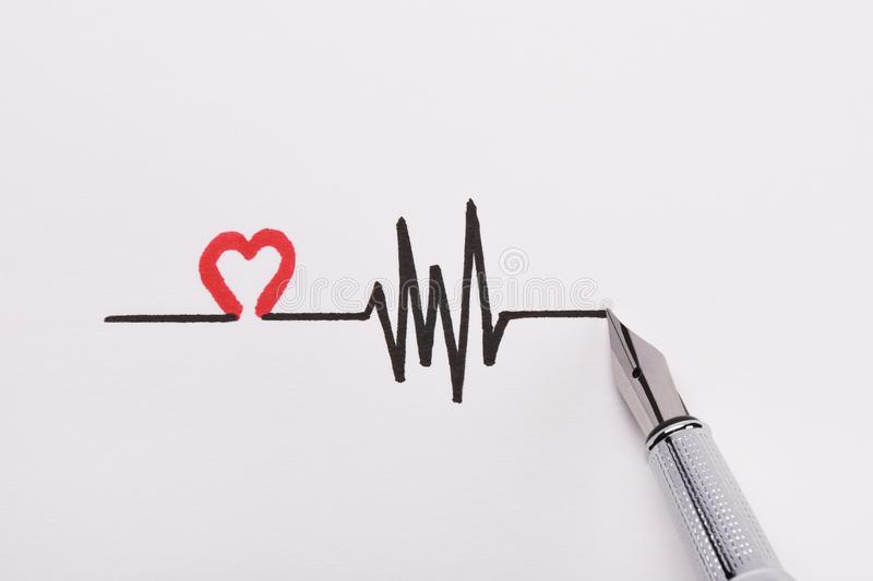 Heart rhythm hand drawing, electrocardiogram, heart beat pulse line concept on white paper stock photography