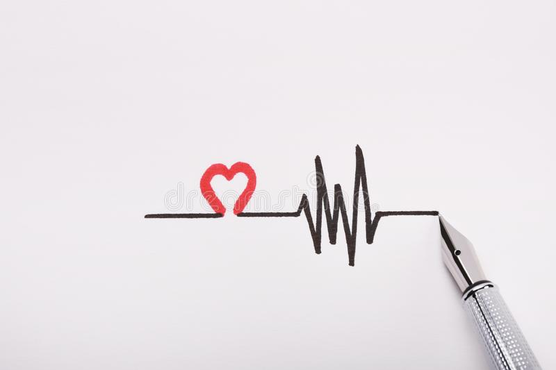 Heart rhythm hand drawing, electrocardiogram, heart beat pulse line concept on white paper royalty free stock image