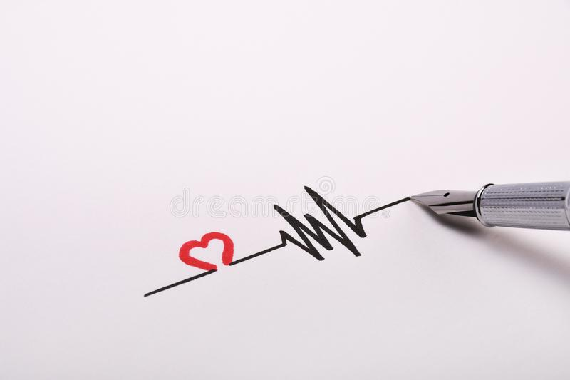 Heart rhythm hand drawing, electrocardiogram, heart beat pulse line concept on white paper royalty free stock photography