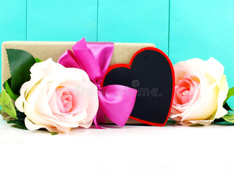 Heart and roses flower with gift box. On blue background royalty free stock photos
