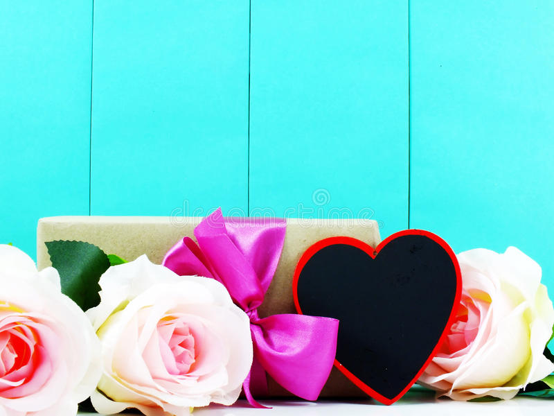 Heart and roses flower with gift box. On blue background stock photos