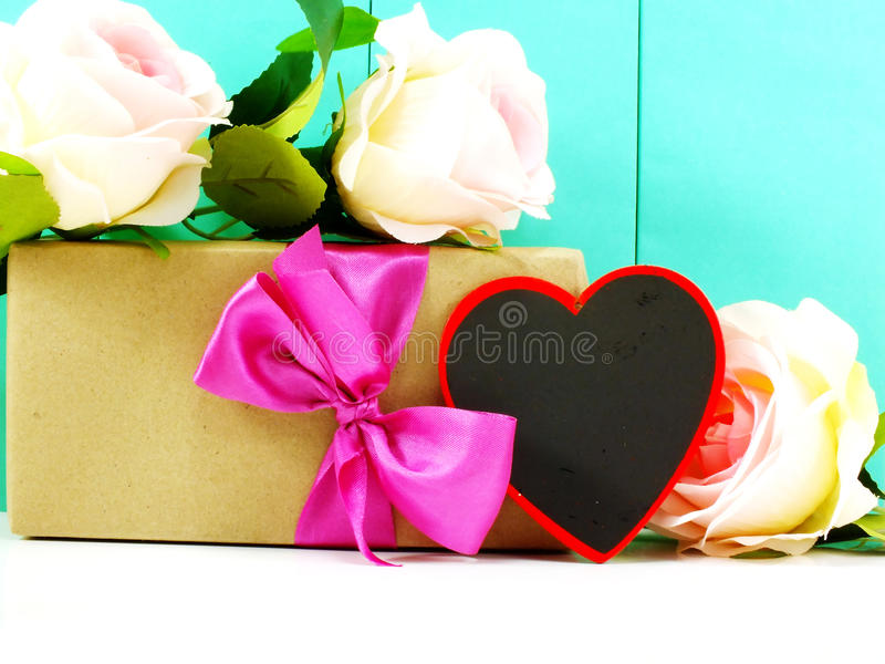 Heart and roses flower with gift box. On blue background royalty free stock image