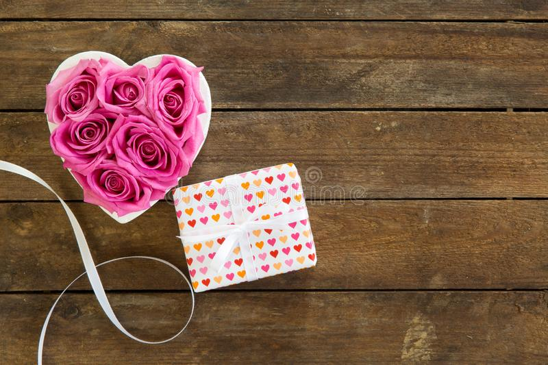 Heart of roses in pink with gift box on wooden background. Mother`s Day, free text area stock image