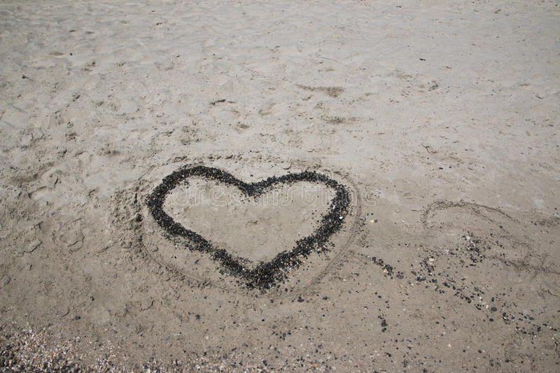 A Heart In The Sand On A Beach. A heart made out of rocks in the sand on a beach stock image