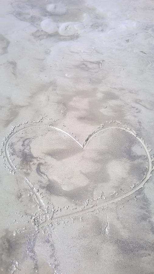 Heart in the sand. Heart drawn in the sand on wild beach royalty free stock photography