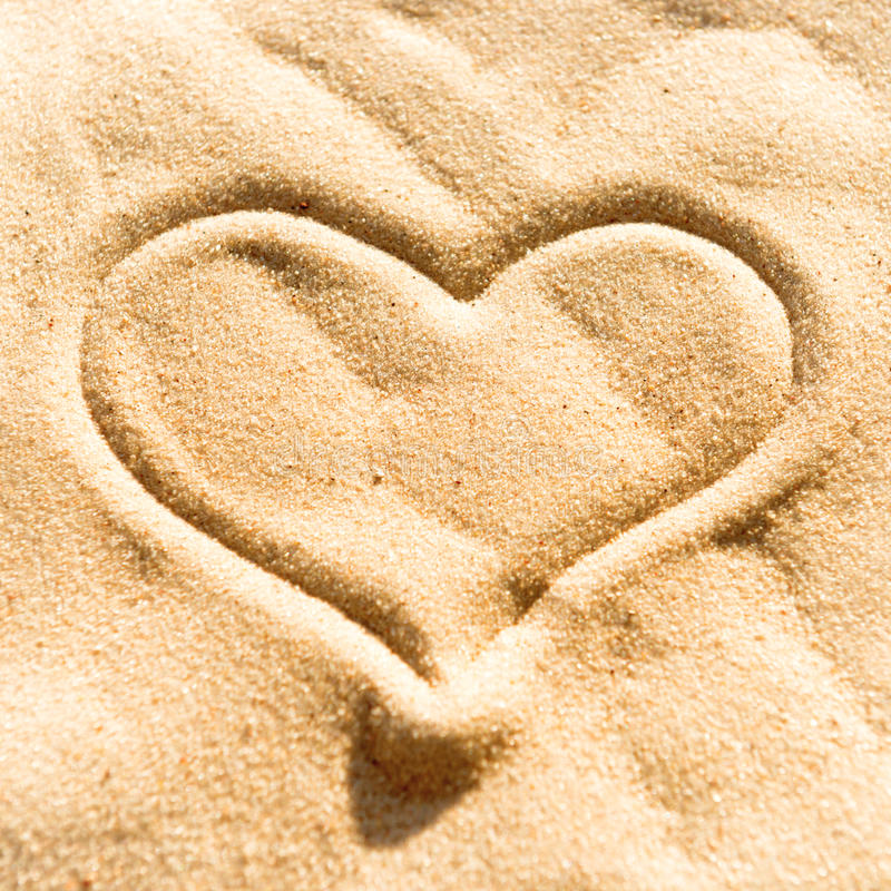 Heart on the sand. Heart sign drawing on the yellow beach sand royalty free stock images