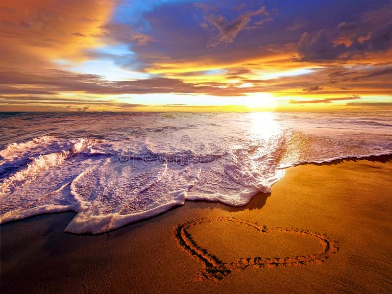 Heart in the sand at sunset stock image