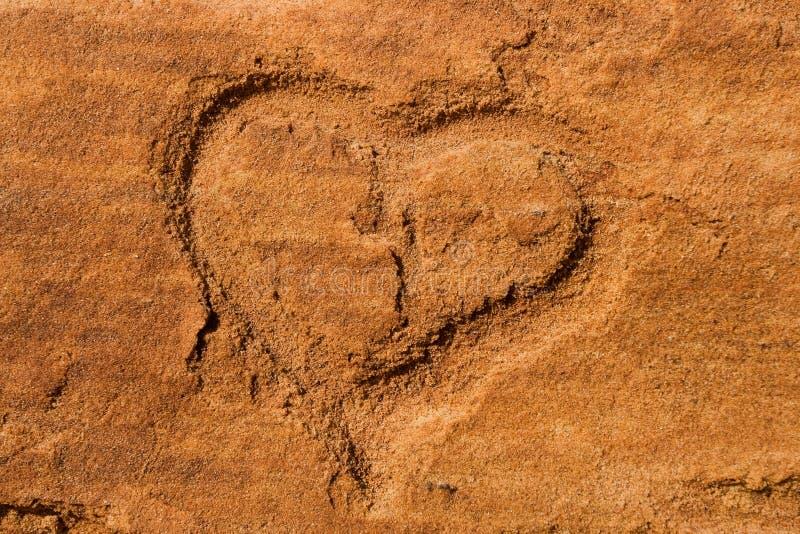 Heart scraped into sandstone. Shape of an heart scraped into the red sandstone stock images