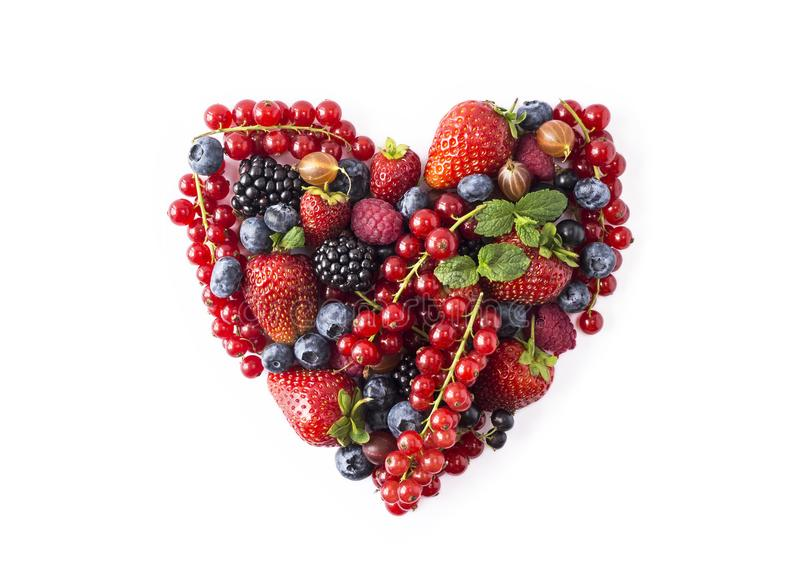 Heart shape assorted berry fruits on white background. Berries in heart shape isolated on a white. Ripe blueberries, red currants,. Raspberries, strawberries stock photo