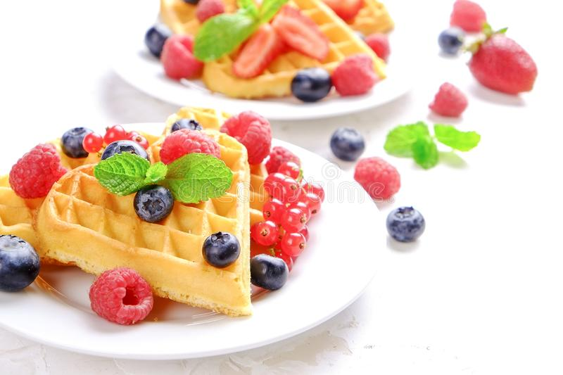Festive breakfast composition with homemade waffles and variety of different summer berries and mint leaves. stock images