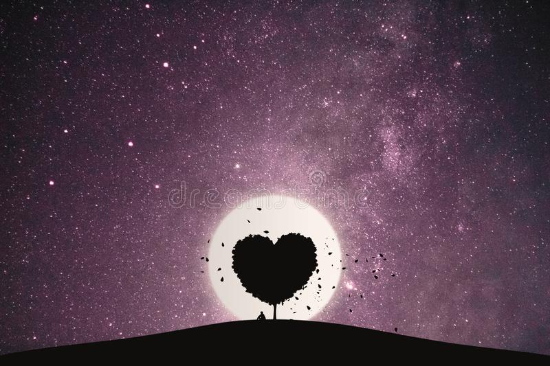 Heart shape of big tree and alone man sitting on a mountain under love tree landscape with fantasy night sky and full moon. royalty free stock photography