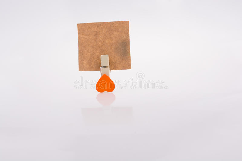 Heart shape clothespin attached to a note paper. On a white background stock images