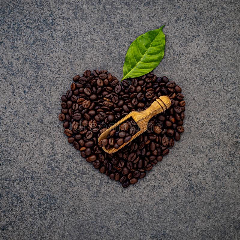Heart shape of coffee beans on dark stone background. Top view with copy space royalty free stock image