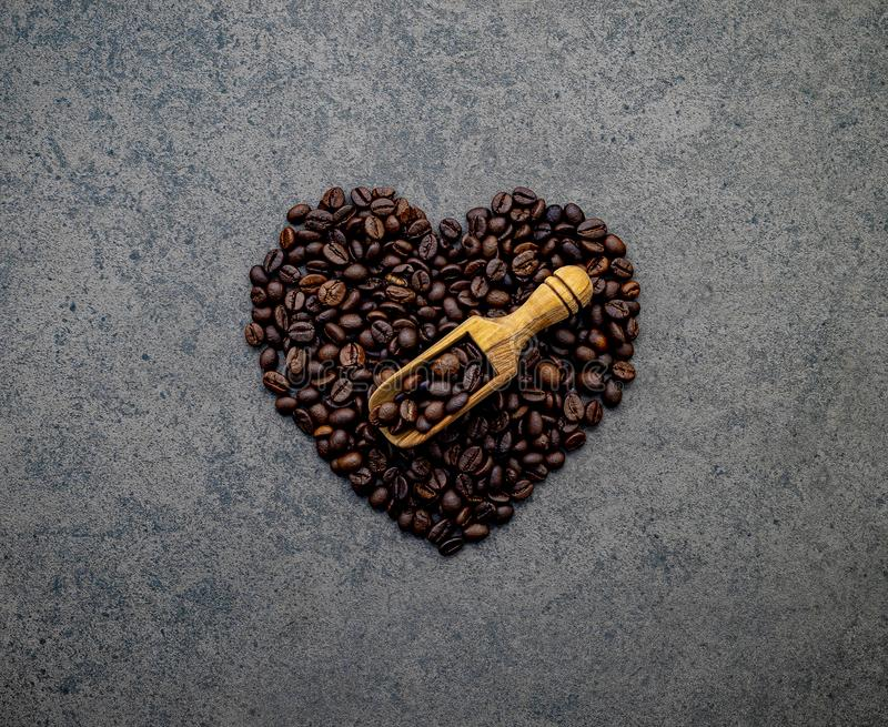 Heart shape of coffee beans on dark stone background. Top view with copy space stock photos