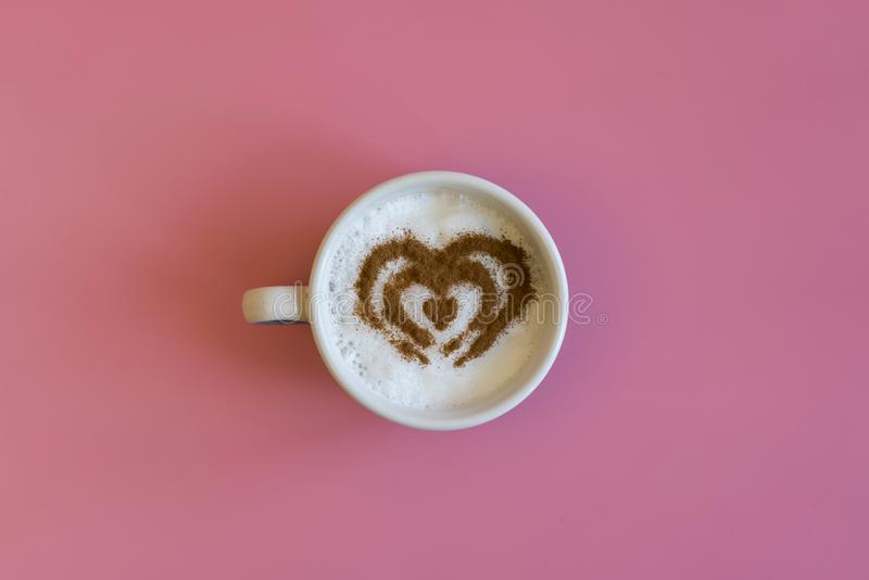 Heart Shape Coffee Cup Concept isolated on pink background. love cup , heart drawing on latte art coffee. royalty free stock photography