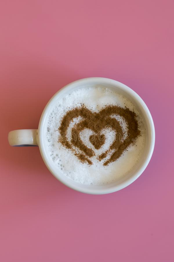 Heart Shape Coffee Cup Concept isolated on pink background. love cup , heart drawing on latte art coffee. vertical photo royalty free stock image