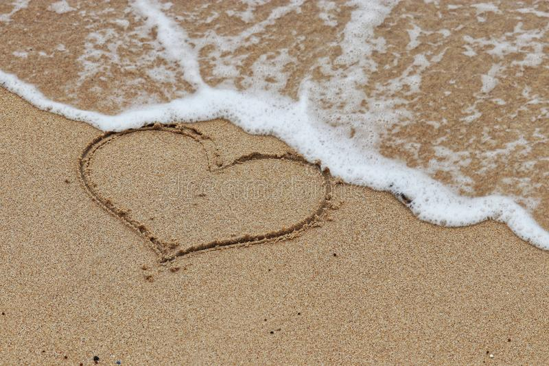 Heart shape on a sandy beach and incoming sea wave. The concept of fleeting love, holiday romance, romantic travel. Heart shape on Concept of fleeting love stock photography