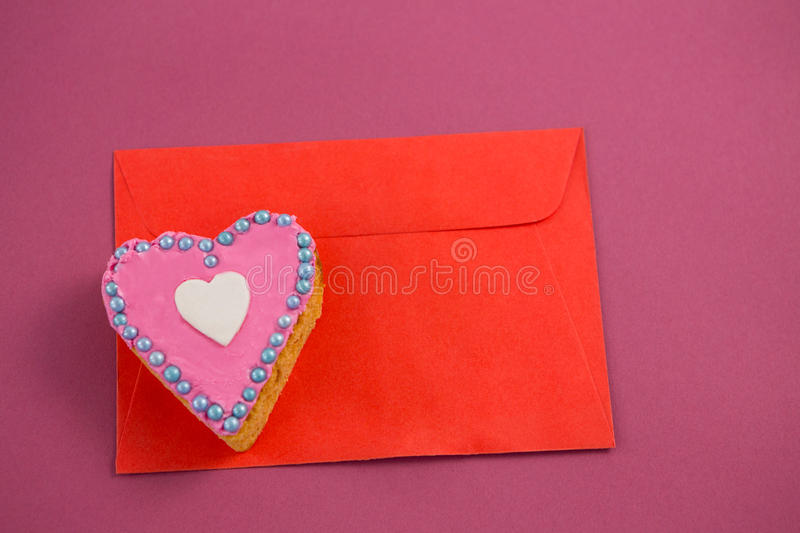 Heart shape cookie on red envelope against pink background stock photos
