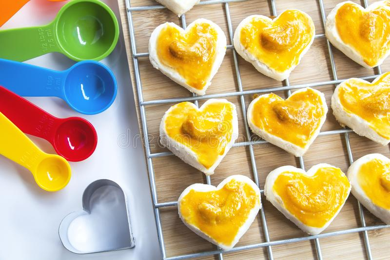 Heart shape cookies with cashew nut or Singapore Cookie and meas. Uring spoon on white table background for valentines day element concept design stock photography