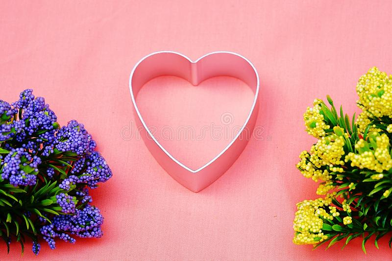 Heart shape decorate with Purple and yellow flowers royalty free stock image