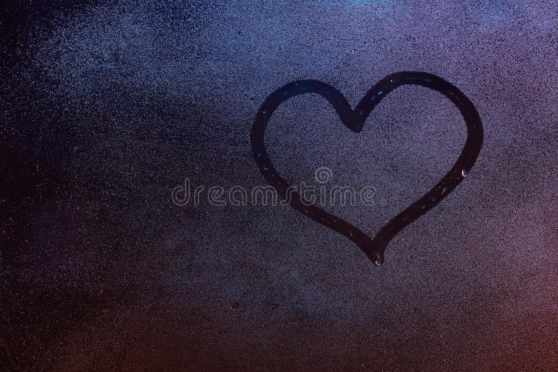 Heart shape drawing. On fog window background. Heart symbol on wet window glass royalty free stock images