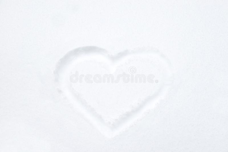 Heart shape drawing on white snow royalty free stock image