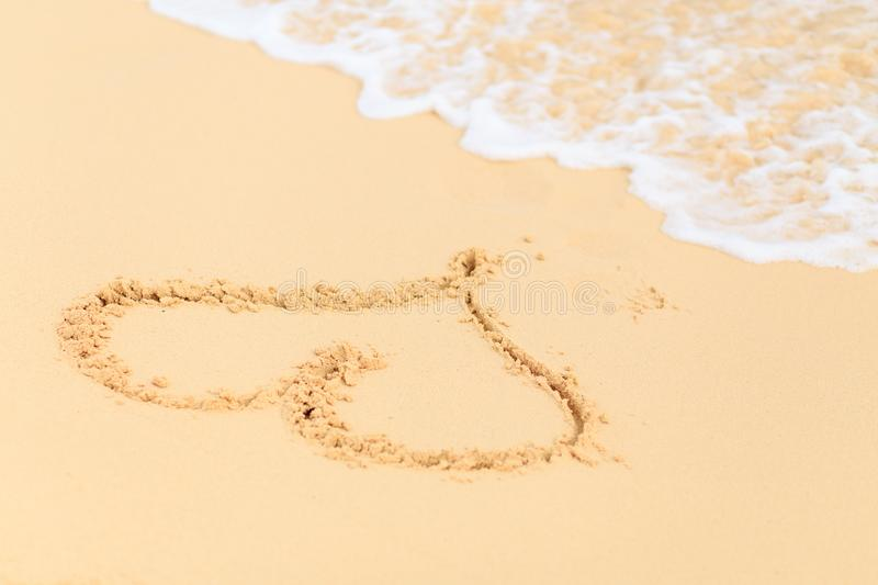 Heart shape drawn on the sand beach before waves royalty free stock photography
