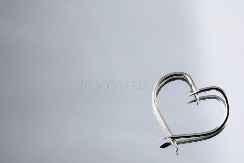 Heart Shape fishing hooks. On mirror stock photo